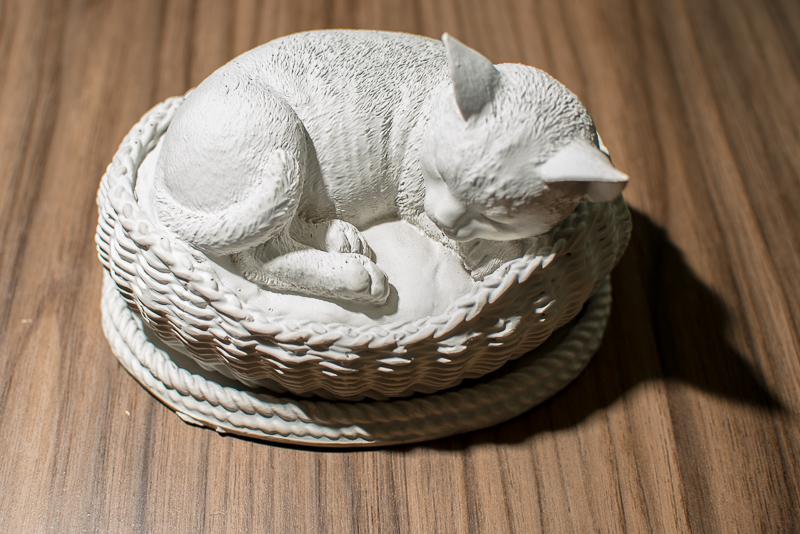 URNA GATO CESTA Com a delicadeza de um gato deitado em sua cestinha esta urna demonstra a confiança que o seu mascote tinha ao acomodar-se nesta posição perto de quem tanto o amou.